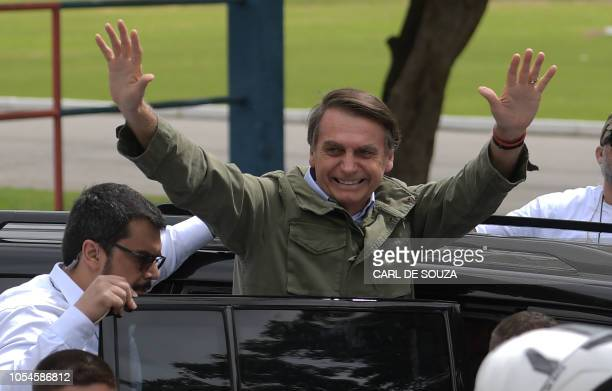 Jair Bolsonaro, far-right lawmaker and presidential candidate for the Social Liberal Party , waves to supporters during the second round of the...