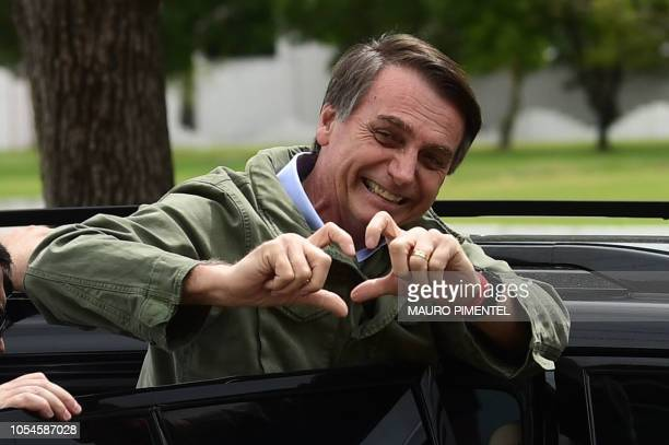 TOPSHOT Jair Bolsonaro farright lawmaker and presidential candidate for the Social Liberal Party gestures to supporters during the second round of...