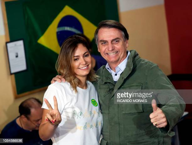 Jair Bolsonaro farright lawmaker and presidential candidate of the Social Liberal Party and his wife Michelle pose as they arrive to cast their votes...