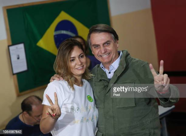 Jair Bolsonaro farright lawmaker and presidential candidate of the Social Liberal Party poses with his wife Michelle as they arrive to cast their...