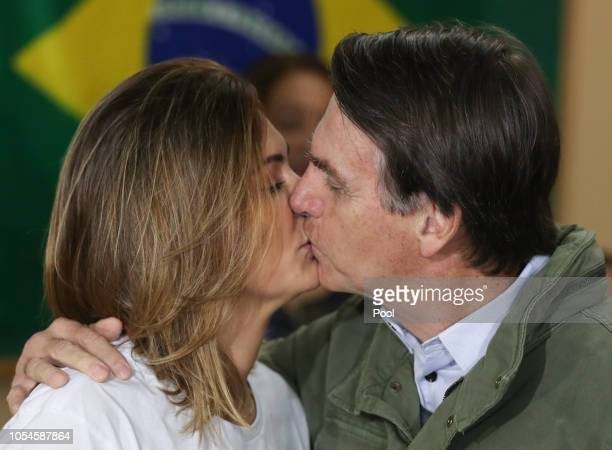 Jair Bolsonaro farright lawmaker and presidential candidate of the Social Liberal Party and his wife Michelle kiss before casting their votes on...