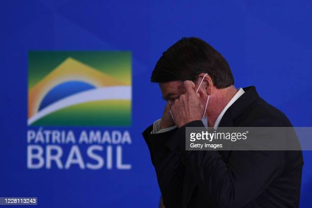 Jair Bolsonaro, President of Brazil adjusts his face mask during a ceremony to sanction the provisional measure that facilitates access to bank...