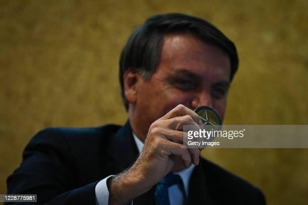 Jair Bolsonaro President of Brazil holds a Niobium coin received as a gift during the launch ceremony of the Mineracao e Desenvolvimento Program on...