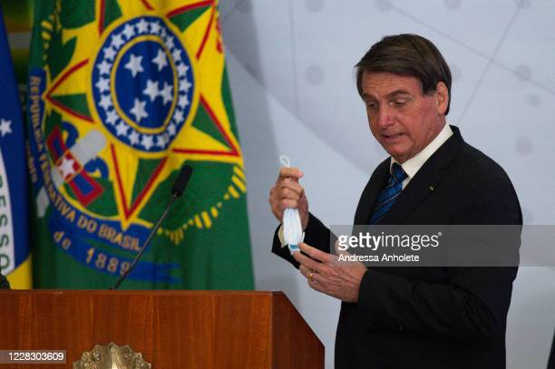 Jair Bolsonaro, President of Brazil, removes his protective mask during launch of the Programa Norte Conectado amidst the coronavirus pandemic at the...