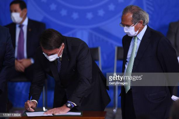 Jair Bolsonaro, President of Brazil signs a bill next to Paulo Guedes Minister of Economy of Brazil during a ceremony to sanction the provisional...