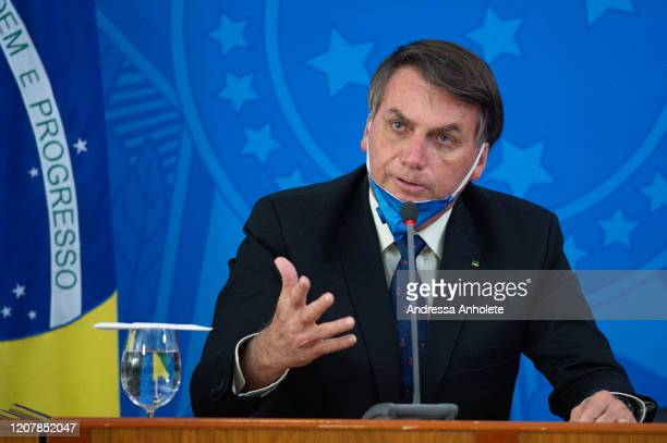 Jair Bolsonaro President of Brazil takes off his protective mask to speak to journalists during a press conference about outbreak of the coronavirus...