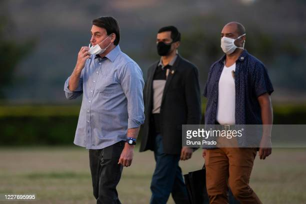 Jair Bolsonaro President of Brazil touches his face mask in front of the official residence after testing positive for coronavirus in Alvorada Palace...