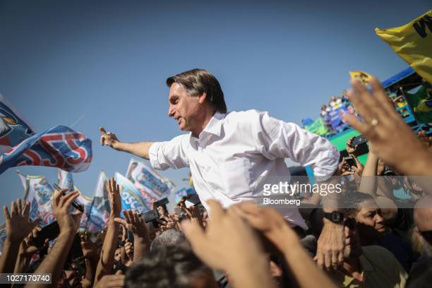 Jair Bolsonaro presidential candidate for the Social Liberal Party waves to supporters during a campaign rally in Taguatinga Brazil on Wednesday Sept...