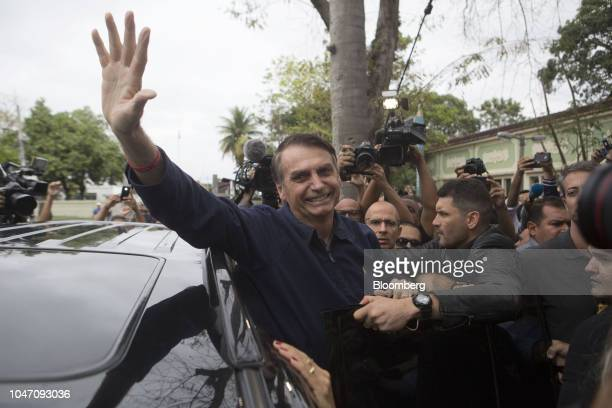 Jair Bolsonaro presidential candidate for the Social Liberal Party waves as he leaves a polling station after casting his ballot during the first...