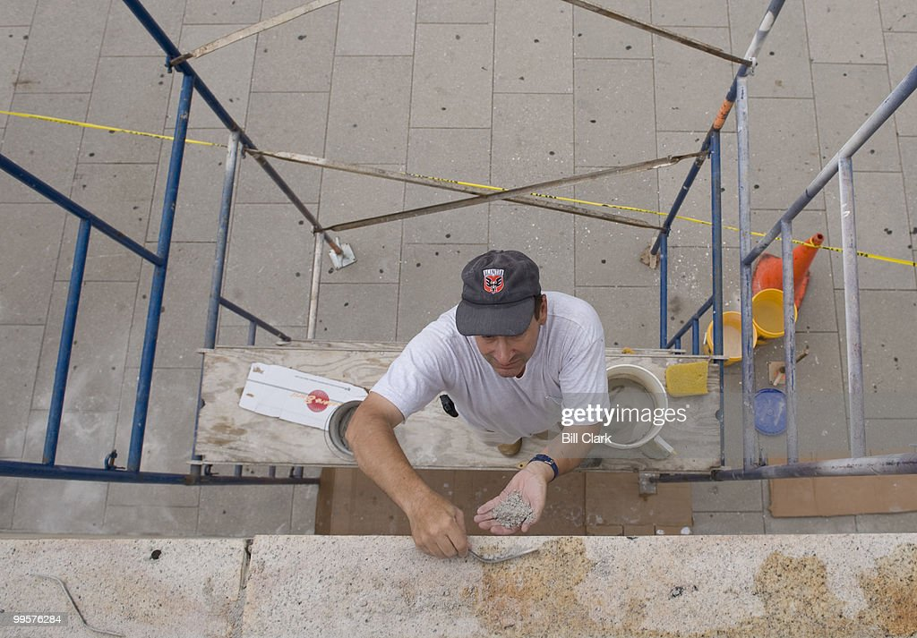Jair Ceron, a stone mason with Firvida Construction Corporation, reseals the joints of the stone work of the Postal Museum Building on Massachussetts Ave. at North Capitol Street on Thursday, Aug. 7, 2008.