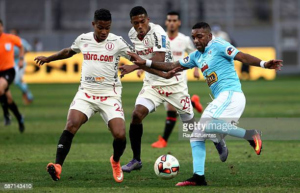 Jair Cespedes of Sporting Cristal struggles for the ball with Andy Polo of Universitario during a match between Universitario and Sporting Cristal as...
