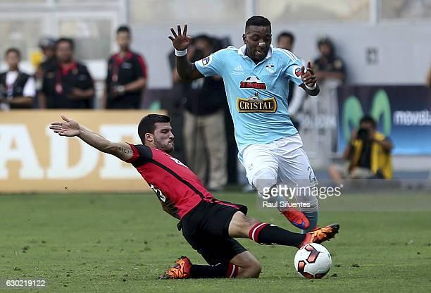 Jair Cespedes of Sporting Cristal struggles for the ball with Bernardo Cuesta of FBC Melgar during a second leg final match between Sporting Cristal...
