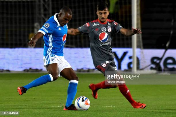 Jair Palacios of Millonarios passes the ball while defended by Kevin Ramirez of America de Cali during the friendly match between Millonarios and...