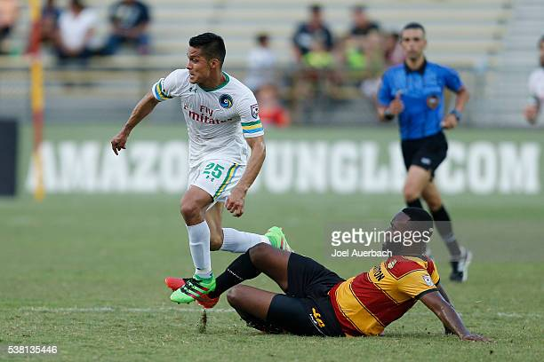 Jairo Arrieta of the New York Cosmos runs past Gale Agbossoumonde of the Fort Lauderdale Strikers as he chases a loose ball during first half action...