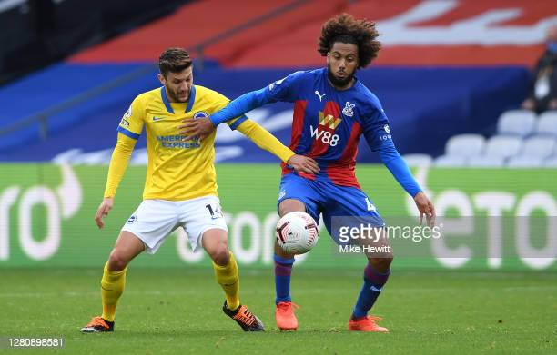 Jairo Riedewald of Crystal Palace is challenged by Adam Lallana of Brighton and Hove Albion during the Premier League match between Crystal Palace...