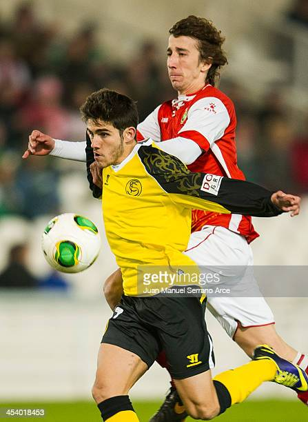 Jairo Samperio of Sevilla FC duels for the ball with Javi Barrio of Racing Santander during the Copa del Rey Round of 32 match between Racing...