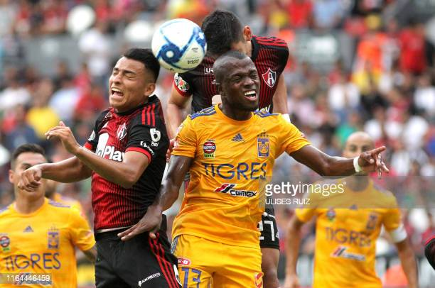 Jairo Torres of Atlas vies for the ball with Enner Valencia of Tigres during their Mexican Apertura 2019 tournament football match at Jalisco...