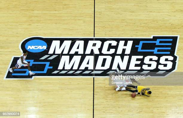 Jairus Lyles of the UMBC Retrievers and Isaiah Wilkins of the Virginia Cavaliers dive for a loose ball during the first round of the 2018 NCAA Men's...