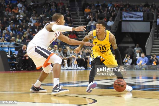 Jairus Lyles of the UMBC Retrievers dribbles around Devon Hall of the Virginia Cavaliers during the first round of the 2018 NCAA Men's Basketball...
