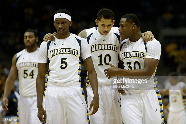 JaJuan Johnson of the Marquette Golden Eagles Juan Anderson and Deonte Burton huddle up before the start of play during the second half against the...