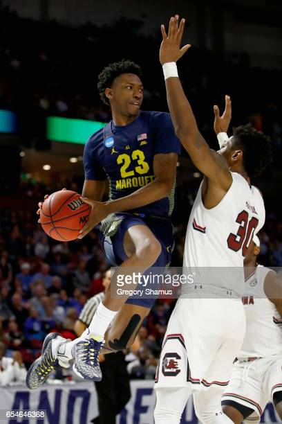 Jajuan Johnson of the Marquette Golden Eagles passes against Chris Silva of the South Carolina Gamecocks in the first half during the first round of...