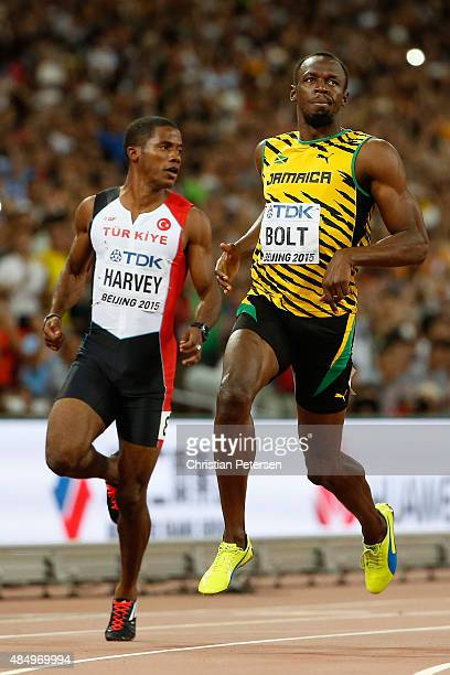 Jak Ali Harvey of Turkey and Usain Bolt of Jamaica cross the finish line in the Men's 100 metres semi-final during day two of the 15th IAAF World...