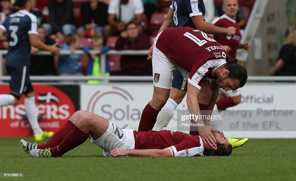 Jak McCourt of Northampton Town lies injured and is consoled by team mate John-Joe O'Toole during the Sky Bet League One match between Northampton Town and Southend United at Sixfields on September 24, 2016 in Northampton, England.