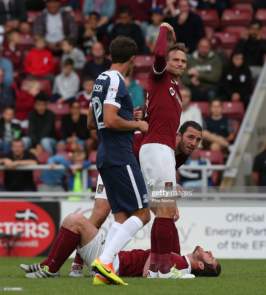 Jak McCourt of Northampton Town lies injured as team mate Matt Taylor motions to the bench during the Sky Bet League One match between Northampton Town and Southend United at Sixfields on September 24, 2016 in Northampton, England.
