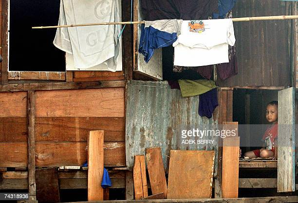 Jakarta, Java, INDONESIA: A boy peers from the window of his dwelling at a slum in Jakarta, 25 May 2007. Despite the progress made in recovering from...