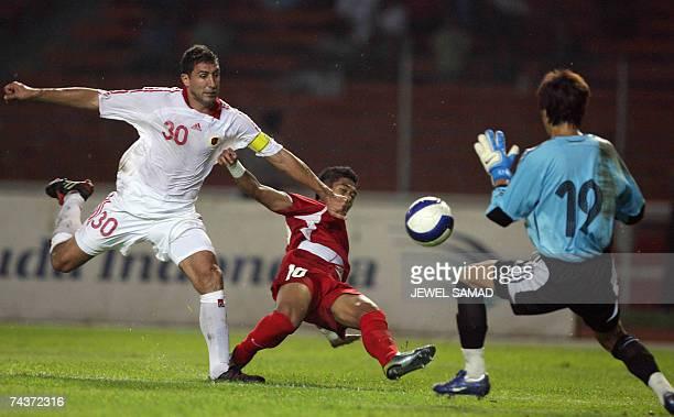 Indonesian Bambang Pamungkas vies for the ball with Hong Kong's Cordeiro Cristiano Preigchadt and goalkeeper Fan Chun Yip during their friendly...