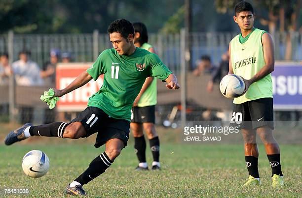 Indonesian national football team captain Ponaryo Astaman kicks a ball as his teammate Bambang Pamungkas looks on during a training session in...