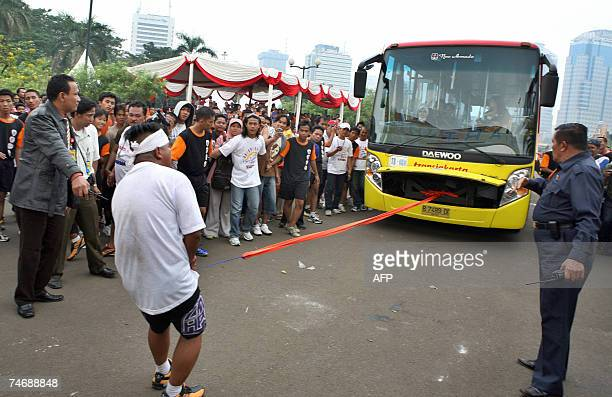 Jaja Stone pulls a 89ton bus with his penis during a strong man contest in Jakarta 17 June 2007 The contest was organized to mark Jakarta's 480th...