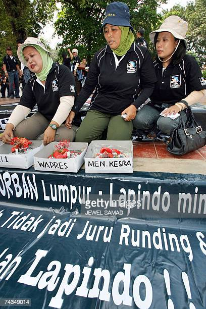 Protesters sit in front of cakes made of mud during a demonstration in Jakarta 29 May 2007 to mark the one year anniversary of the mud volcano...