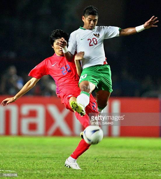 South Korean Kang Minsoo and Indonesian Bambang Pamungkas vief for the ball during their Asian Cup 2007 Group D football match at the Bung Karno...