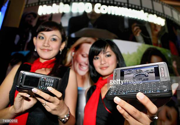 Two models display the new Nokia 'E90' mobile phone sets during a launching ceremony in Jakarta 13 June 2007 Nokia 'E90' communicator launched 13...