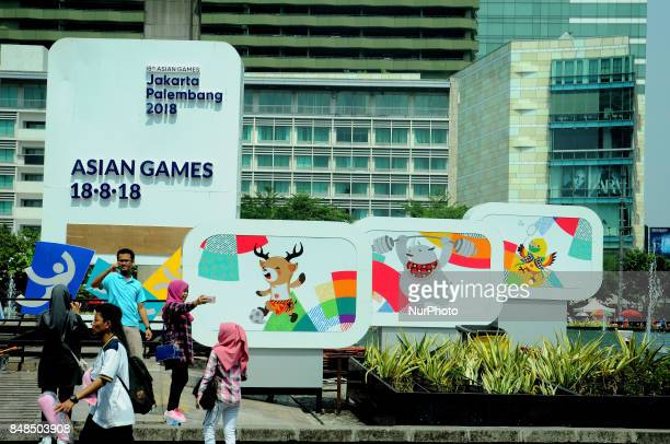 Jakarta residents take pictures in front of the screen countdown the implementation of Asian games installed in the park roundabout monument welcome...