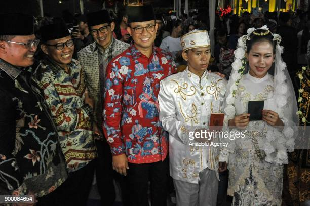 Jakarta's Governor Anies Baswedan and Vice Governor Sandiaga S Uno pose for a photo with participants of mass wedding to mark new year ceremony at...