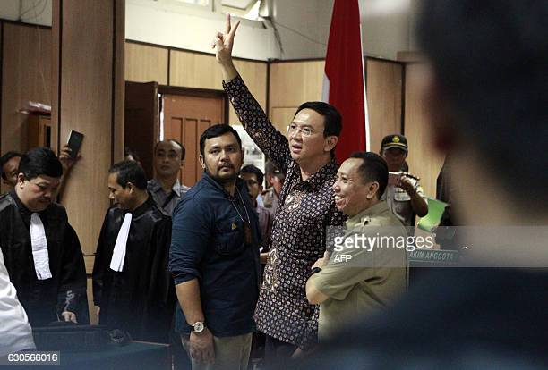Jakarta's Governor Basuki Tjahaja Purnama gestures to visitors inside the courtroom shortly after his ongoing trial at the North Jakarta District...