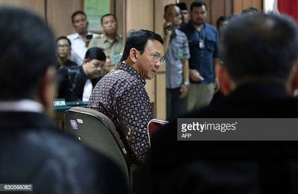 Jakarta's Governor Basuki Tjahaja Purnama looks over at his lawyers inside the courtroom during his ongoing trial at the North Jakarta District Court...