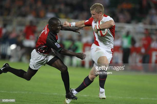 Jake Abbott of England holds off Sidney Ashioya of Kenya to score a try during the IRB Sevens tournament at the Dubai Sevens Stadium on December 4...