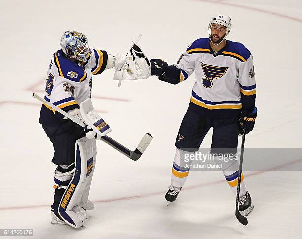 Jake Allen and Robert Bortuzzo of the St Louis Blues celebrate a win over the Chicago Blackhawks during the season opening game at the United Center...