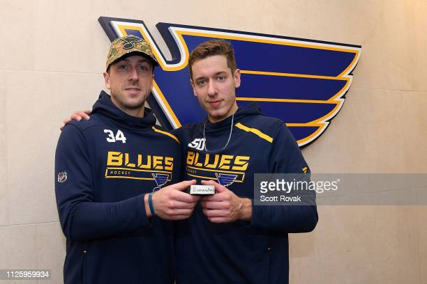 Jake Allen of the St. Louis Blues and Jordan Binnington of the St. Louis Blues hold up a game puck signifying a franchise record eleventh straight...