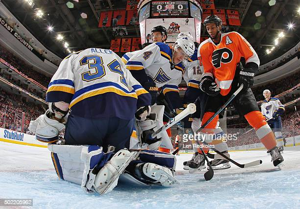Jake Allen of the St Louis Blues covers the loose puck as teammate Carl Gunnarsson defends against Wayne Simmonds of the Philadelphia Flyers on...