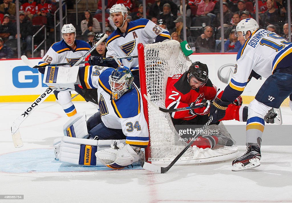 Jake Allen #34 of the St. Louis Blues defends his net as Jay Bouwmeester #19 checks Kyle Palmieri #21 of the New Jersey Devils during the game at the Prudential Center on November 10, 2015 in Newark, New Jersey.