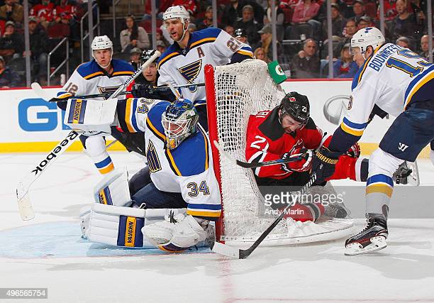 Jake Allen of the St. Louis Blues defends his net as Jay Bouwmeester checks Kyle Palmieri of the New Jersey Devils during the game at the Prudential...