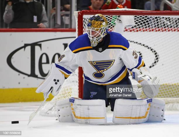 Jake Allen of the St Louis Blues knocks the puck away against the Chicago Blackhawks at the United Center on November 14 2018 in Chicago Illinois The...