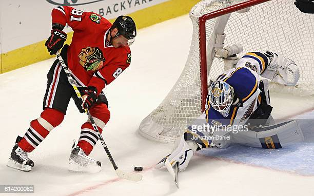 Jake Allen of the St Louis Blues makes a save against Marian Hossa of the Chicago Blackhawks in the third period during the season opening game at...