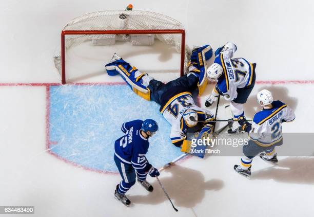 Jake Allen of the St Louis Blues makes a save behind his teammates Patrik Berglund and Kenny Agostino of the St Louis Blues as Connor Brown of the...