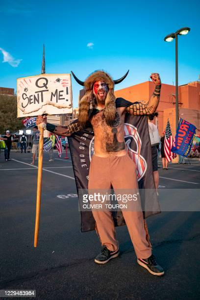Jake Angeli aka Yellowstone Wolf, from Phoenix, holds a QAnon sign, as he presents himself as a shamanist and consultant for the Trump supporters...