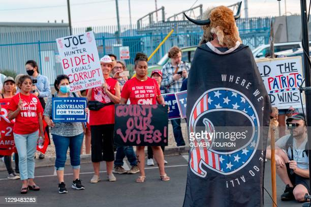Jake Angeli aka Yellowstone Wolf, from Phoenix, wrapped in a QAnon flag, addresses supporters of US President Donald Trump as they protest outside...